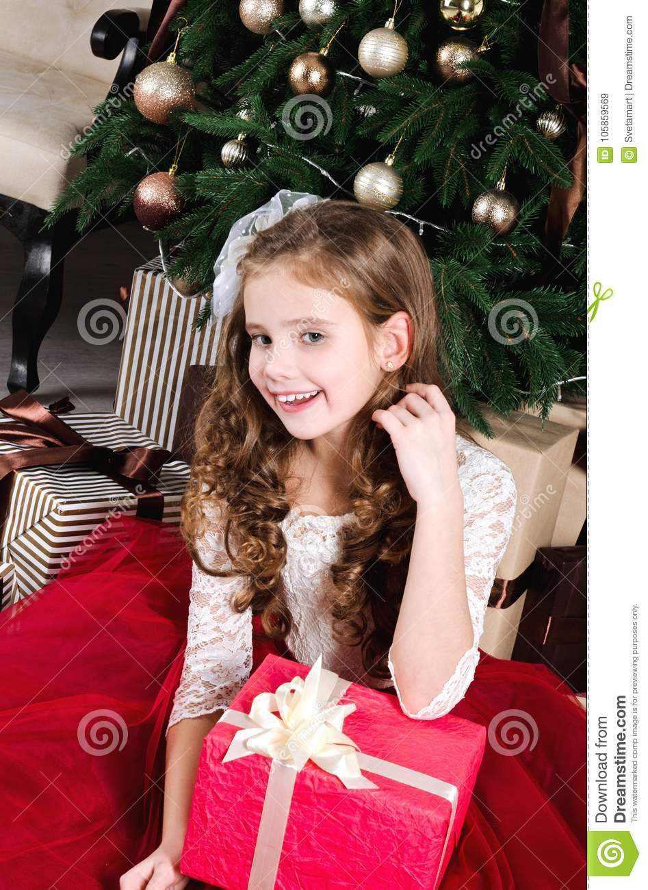 adorable little girl in princess dress with gift box near fir tr
