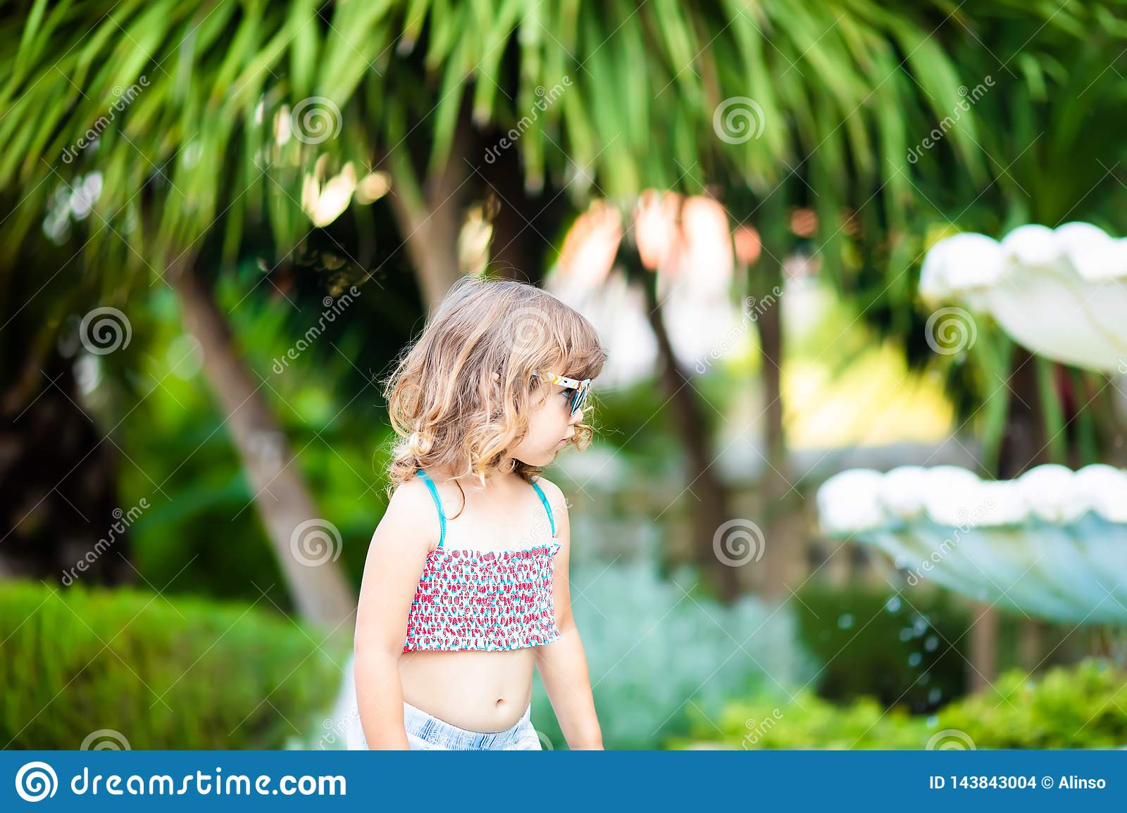 Adorable little girl at the tropical resort, standing by the palm three at the sunny summer day