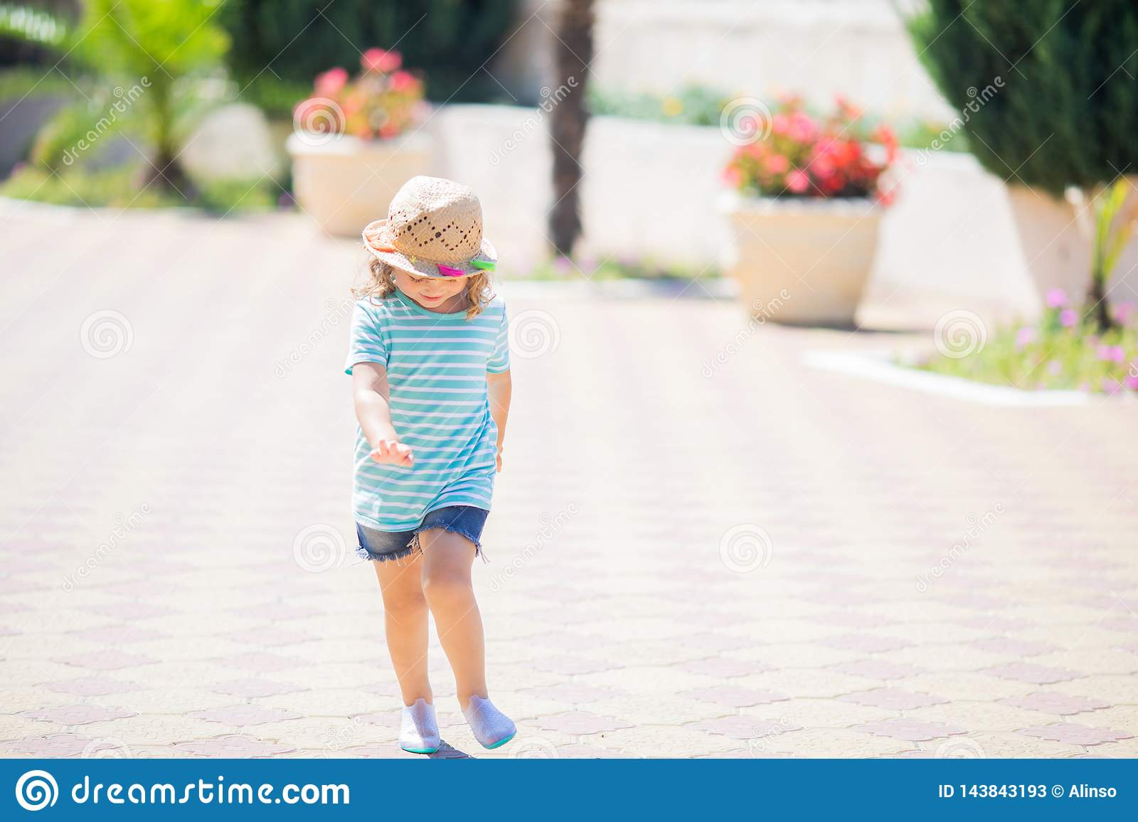 Adorable little girl at the tropical resort, sunny summer day