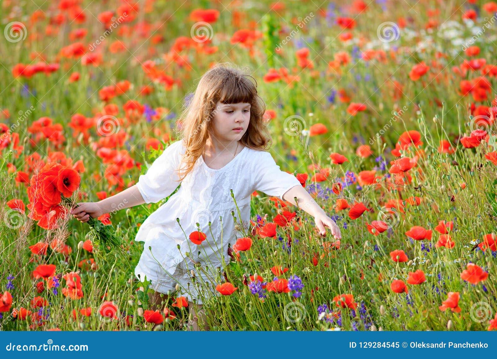Adorable Little Girl In White Dress Playing In Poppy Flower
