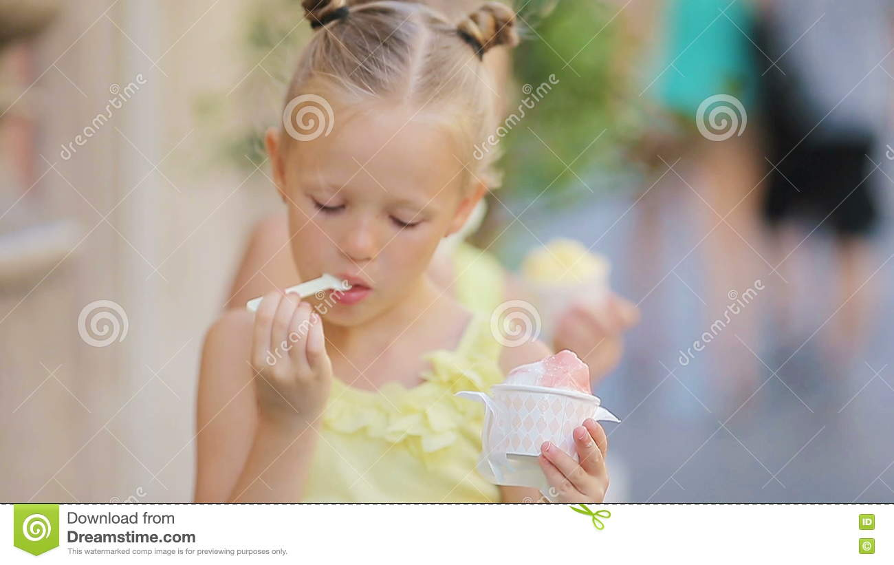 adorable little girls eating ice-cream outdoors at summer. cute kids