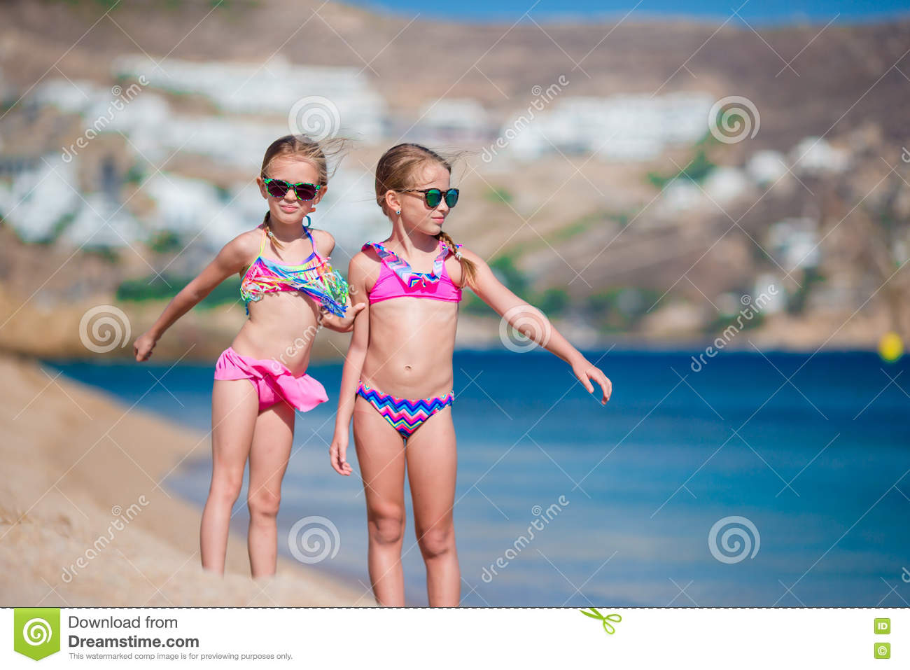 Adorable little girls having fun during beach vacation. Two kids together on greek vacation