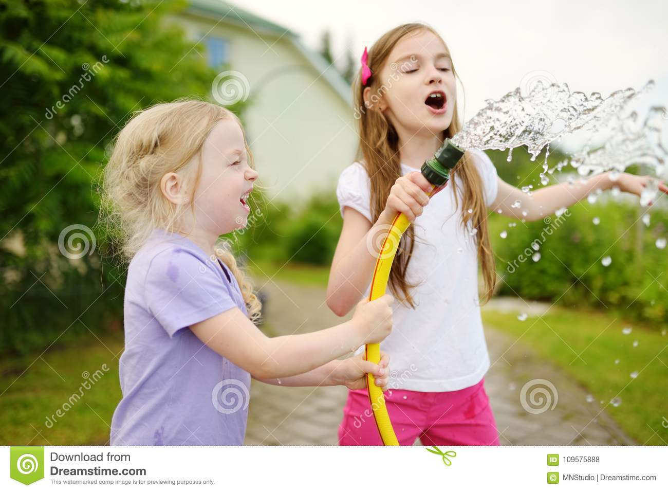 Adorable little girls playing with a garden hose on warm summer day