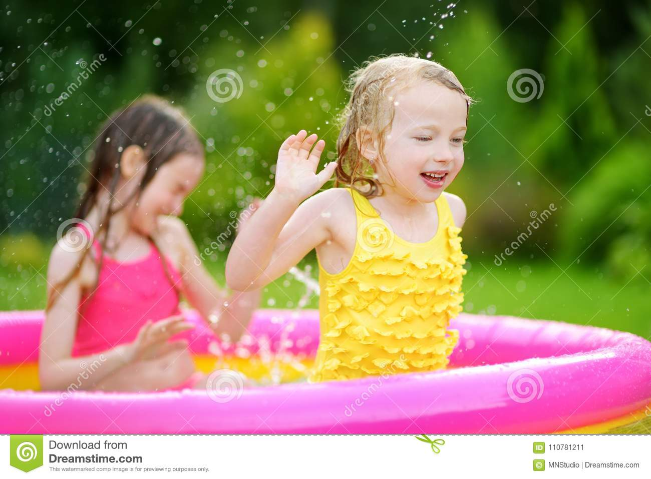 Adorable little girls playing in inflatable baby pool. Happy kids splashing in colorful garden play center on hot summer day.
