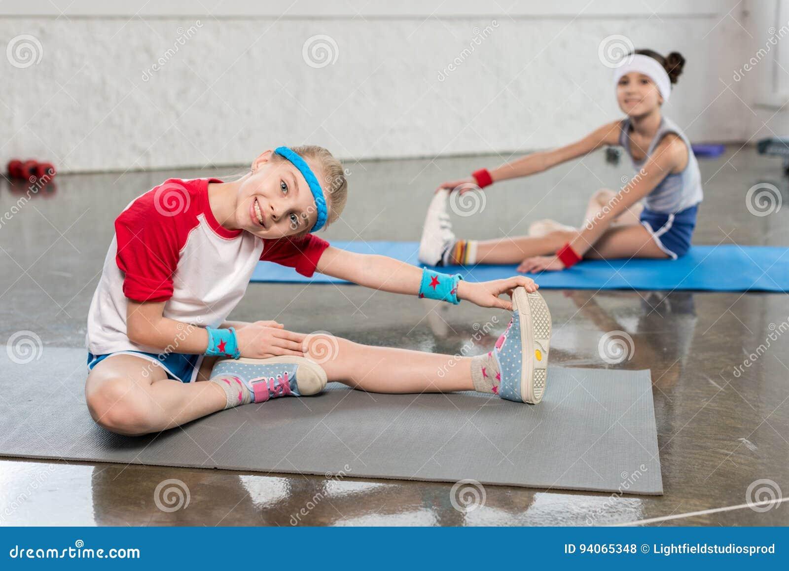 Adorable Little Girls In Sportswear Exercising On Yoga