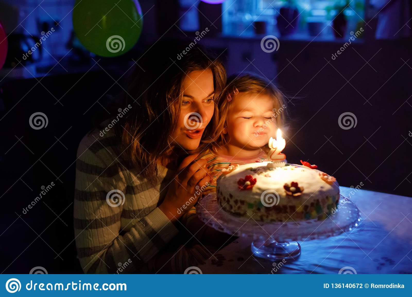 Adorable little toddler girl celebrating second birthday. Baby child daughter and young mother blowing candles on cake