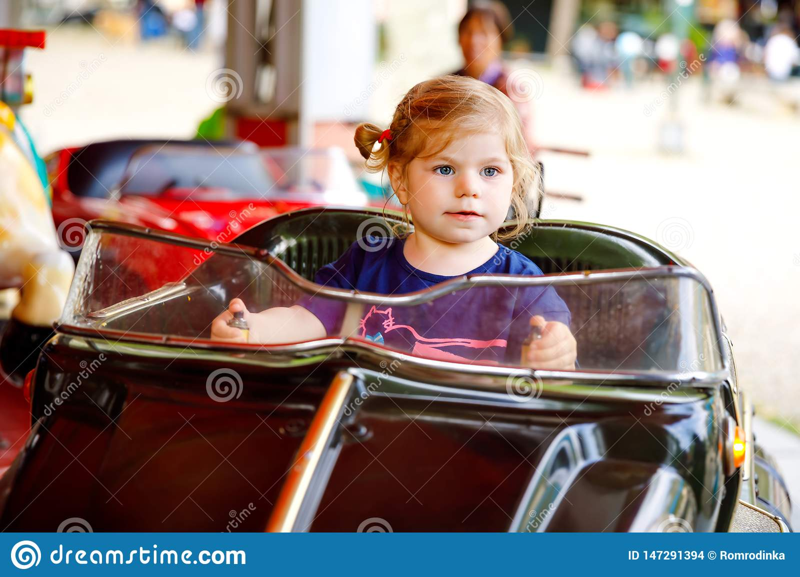 Adorable little toddler girl riding on funny car on roundabout carousel in amusement park. Happy healthy baby child