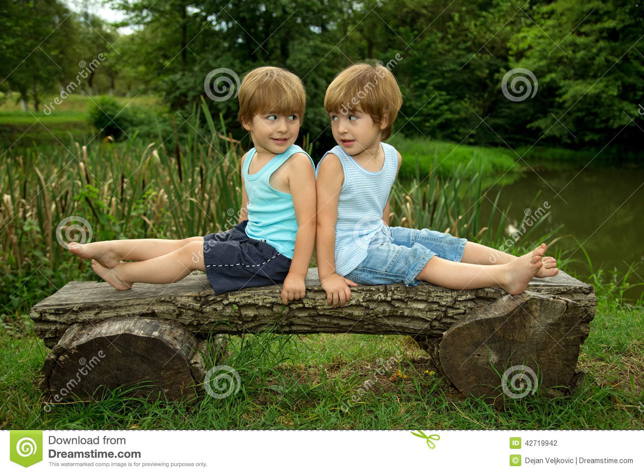 Adorable Little Twin Brothers Sitting On A Wooden Bench ...