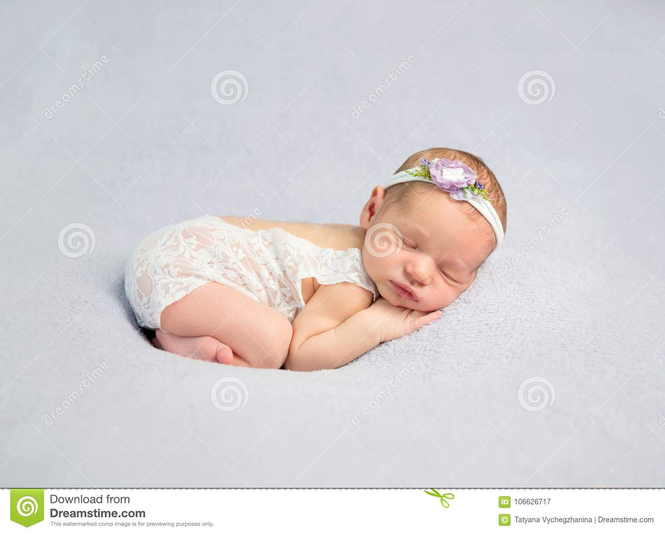 436aace32a74dc Adorable newborn baby girl in white lace bodysuit and headband sleeps on  her side.
