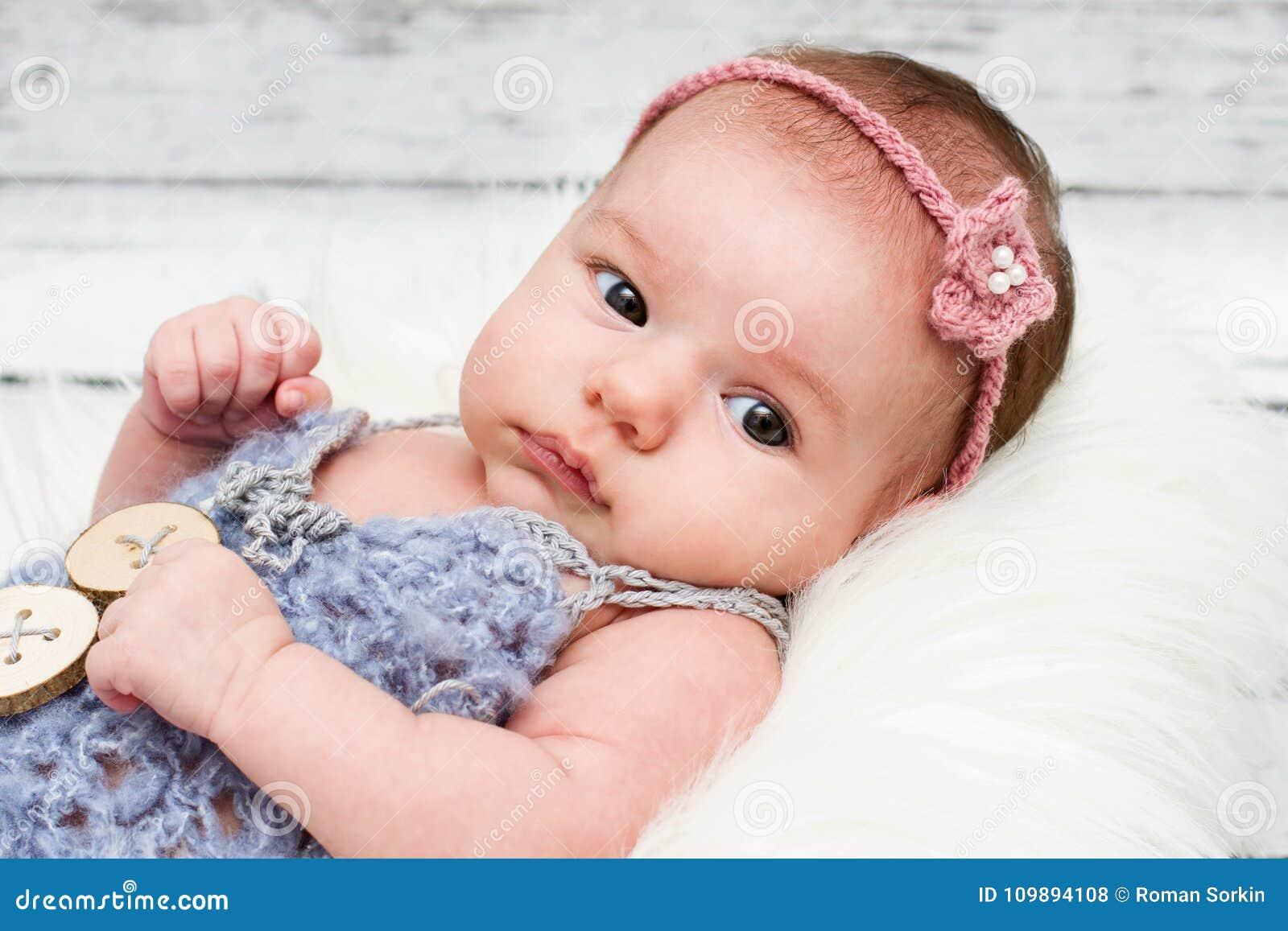 Adorable newborn baby girl looking towards camera