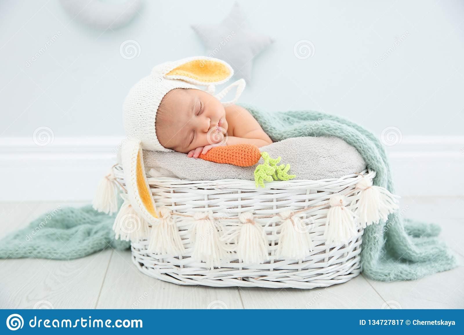 Adorable newborn child wearing bunny ears hat in baby nest