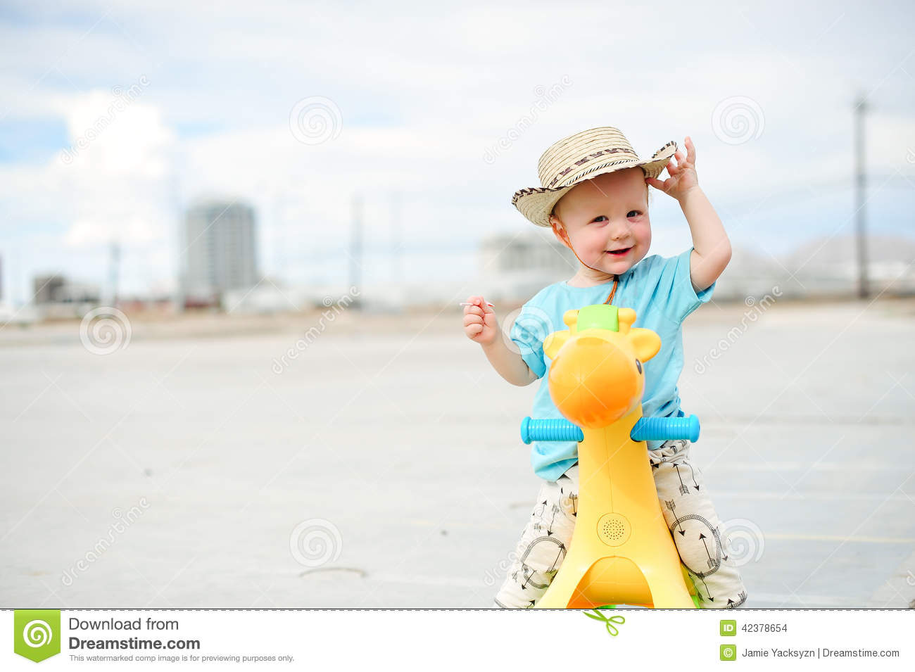 Adorable one year old boy on a plastic horse wearing a cowboy hat. 59df6b791a8