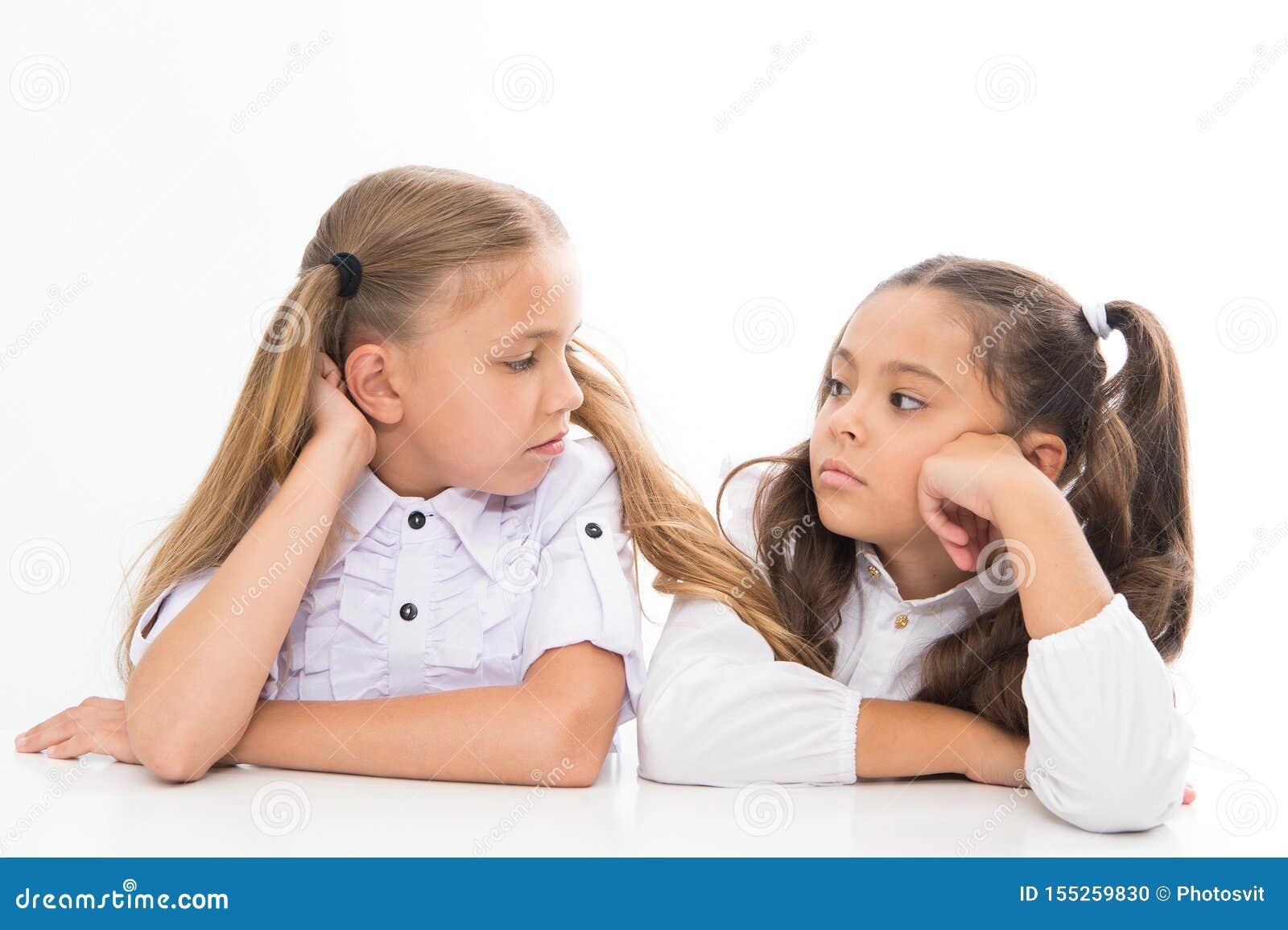 Adorable schoolgirls. Formal style. Happy childhood. Schoolgirls sit at desk white background. Schoolgirls emotional