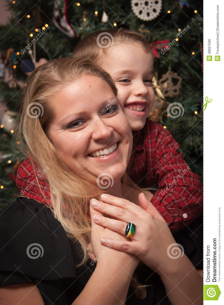 Adorable Son Hugging His Mom in Front Of Christmas Tree