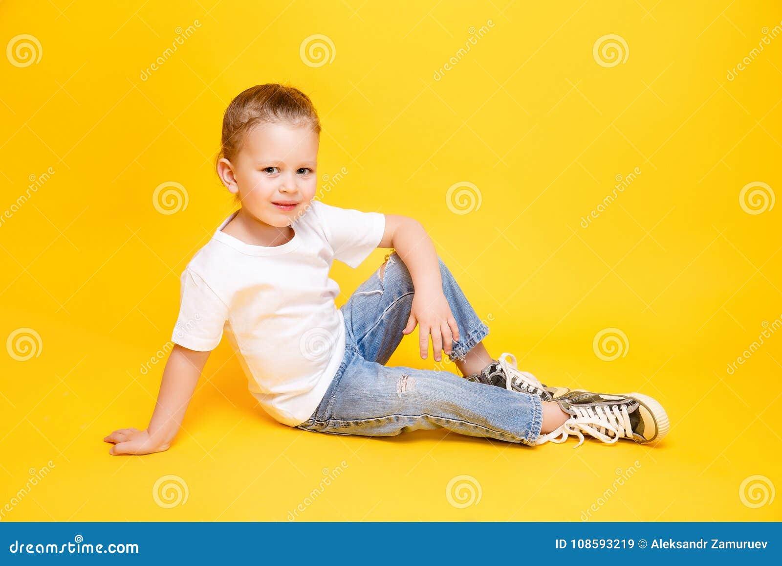 Adorable stylish girl posing on yellow background