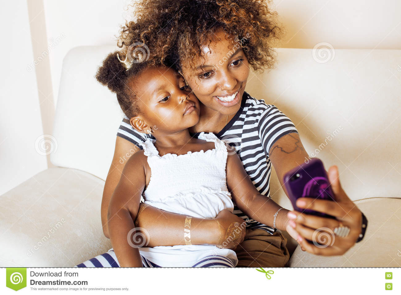 Adorable sweet young afro-american mother with cute little daughter, hanging at home, having fun playing smiling