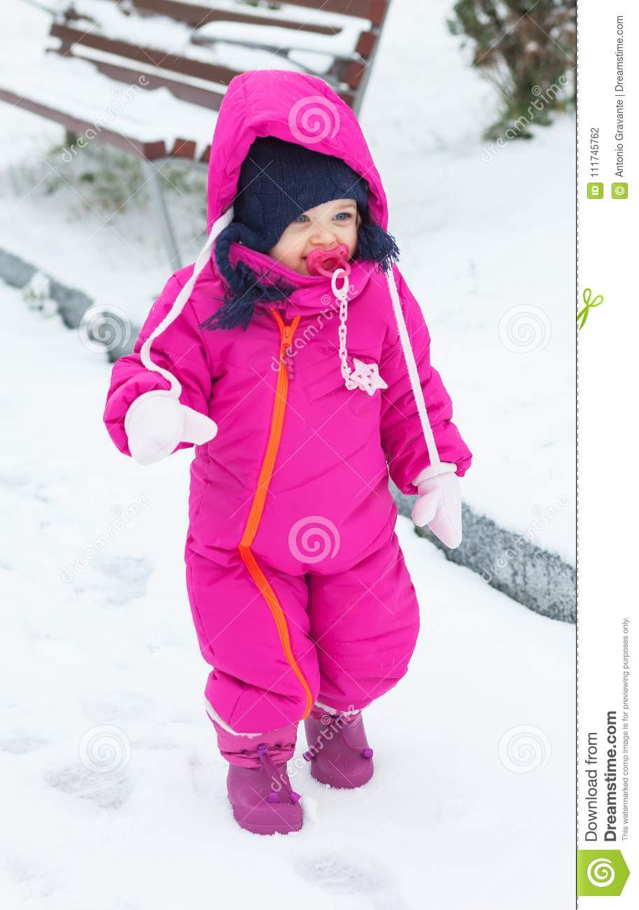 a44f44d75 Toddler Baby Girl In A Magenta Snow Suit Playing On The Snow. Stock ...