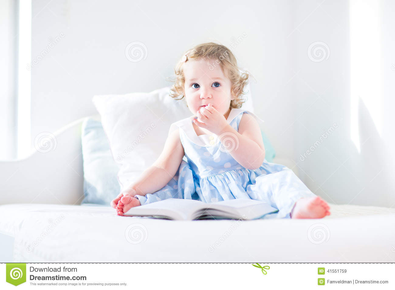 Adorable toddler girl reading book in rocking chair stock for Toddler reading chair