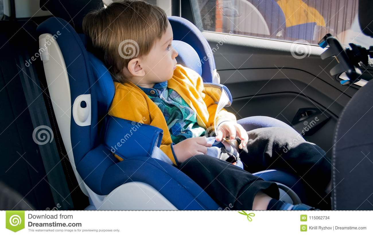 Adorable 2 Years Old Baby Boy Sitting In Car Safety Seat And Looking Out Of The