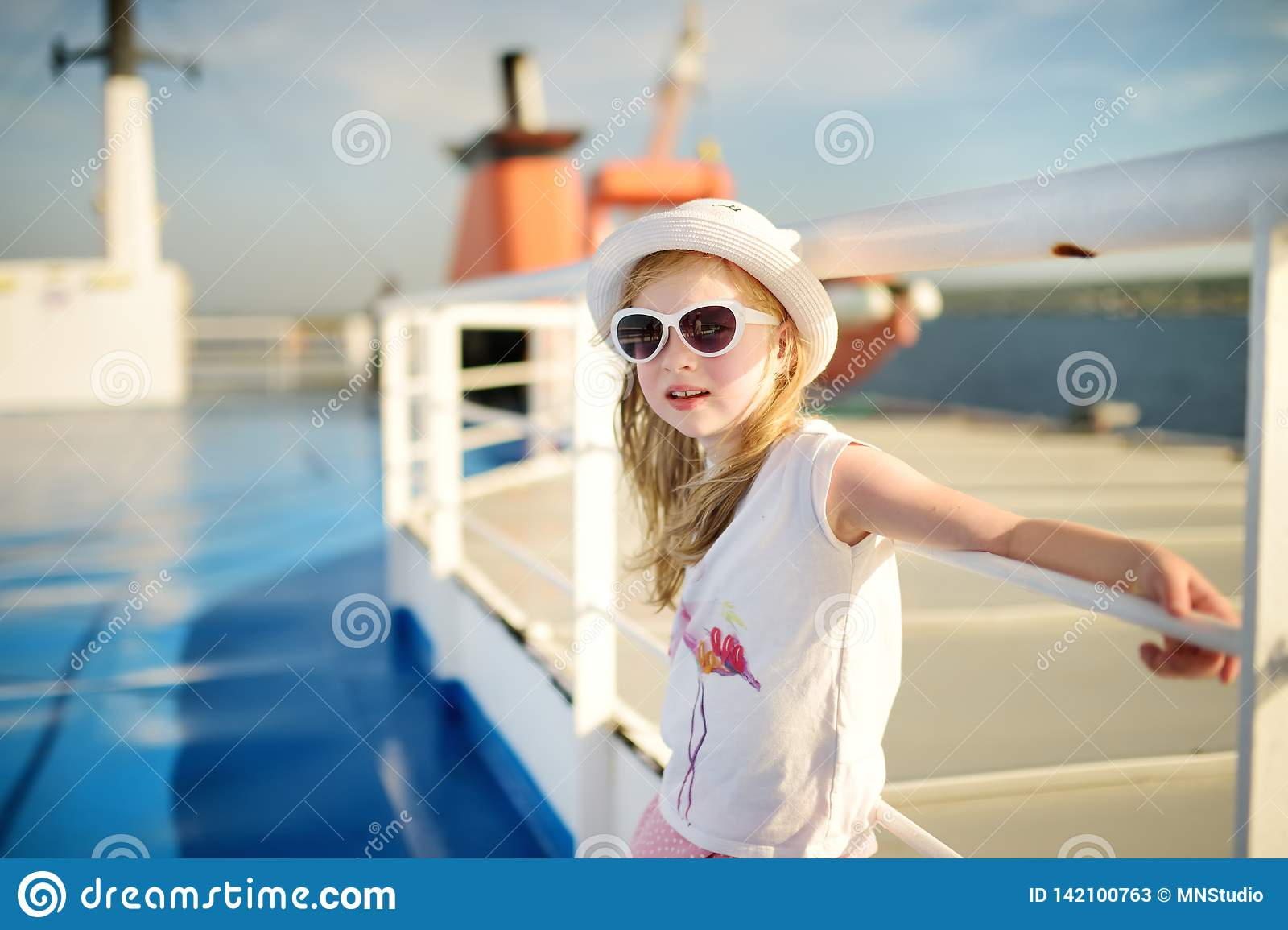 Adorable young girl enjoying ferry ride staring at the sea on sunset. Child having fun on summer family vacation in Greece