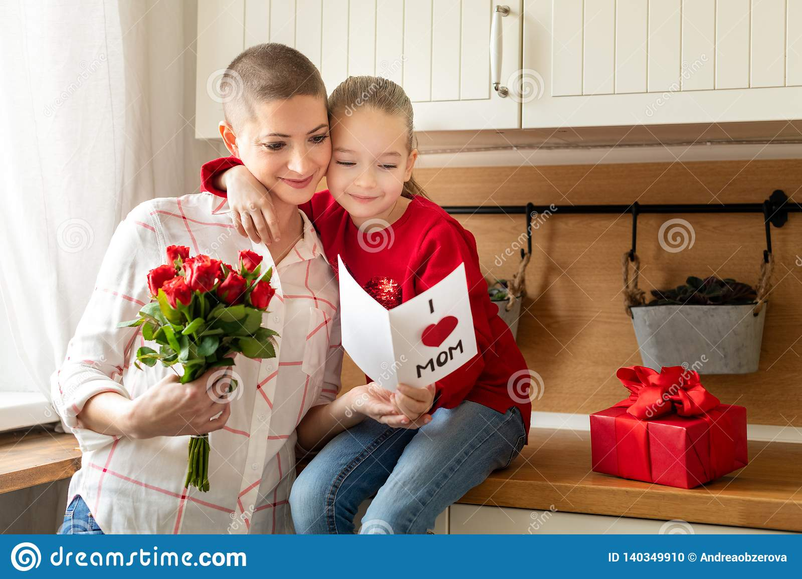 Adorable young girl and her mom, young cancer patient, reading a homemade greeting card. Family concept. Happy Mother`s Day.