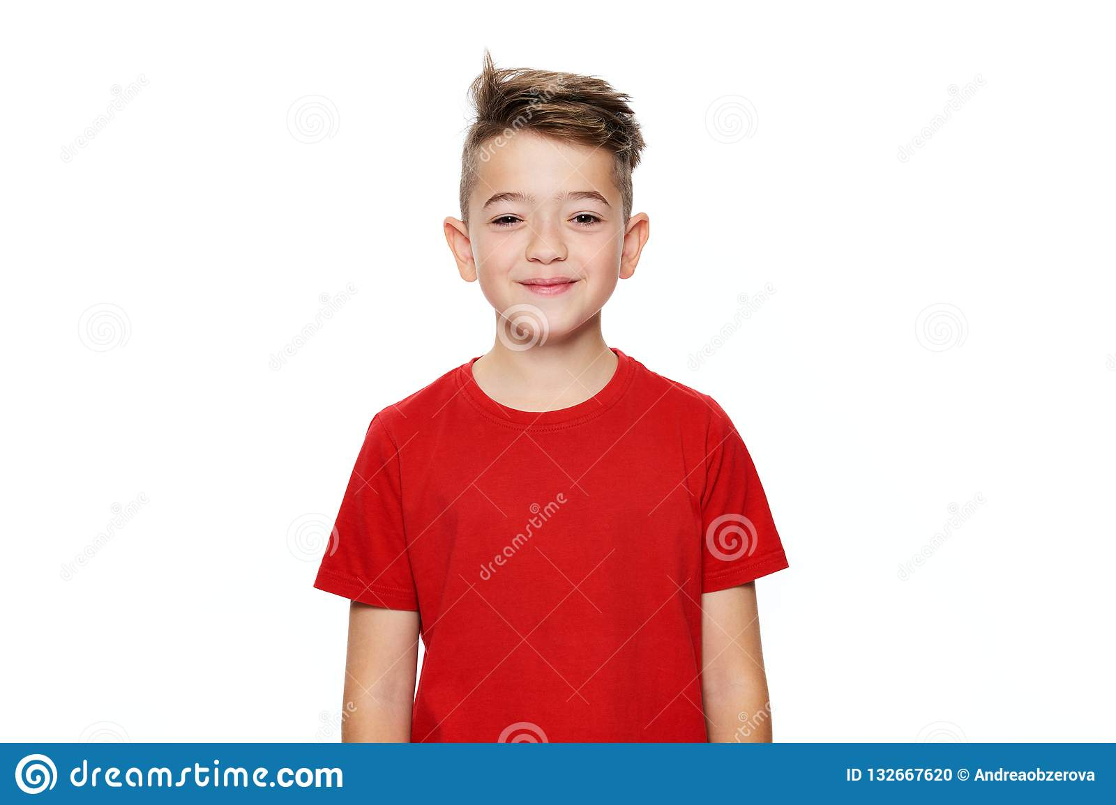 Adorable young teenage boy waist up studio portrait isolated over white background. Handsome boy looking at camera with smile.