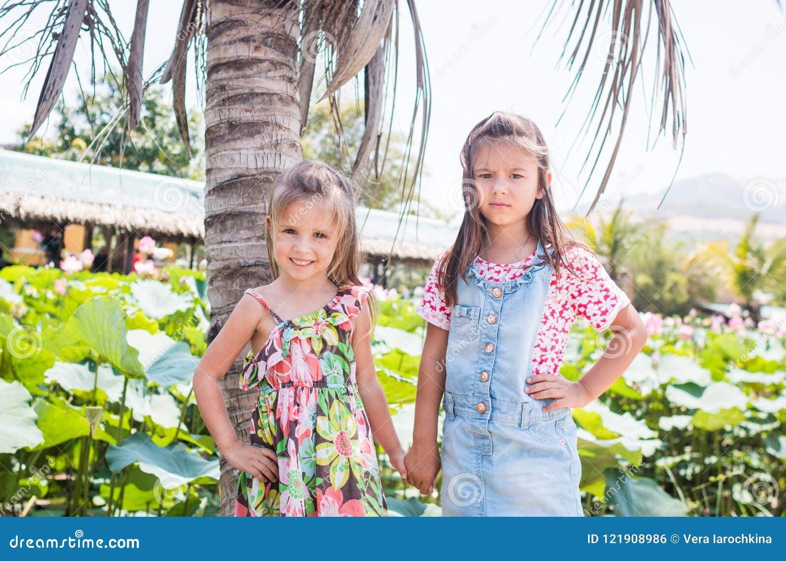Adorables son dos niñas que se colocan al lado de una palma grande, de una sonrisa y de una agujereadas