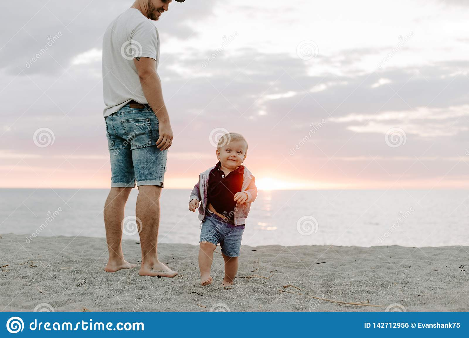Adorably Perfect Young Father and Baby Toddler Son Family Having Fun Time at the Sandy Beach During Sunset Outside By the Ocean Wa