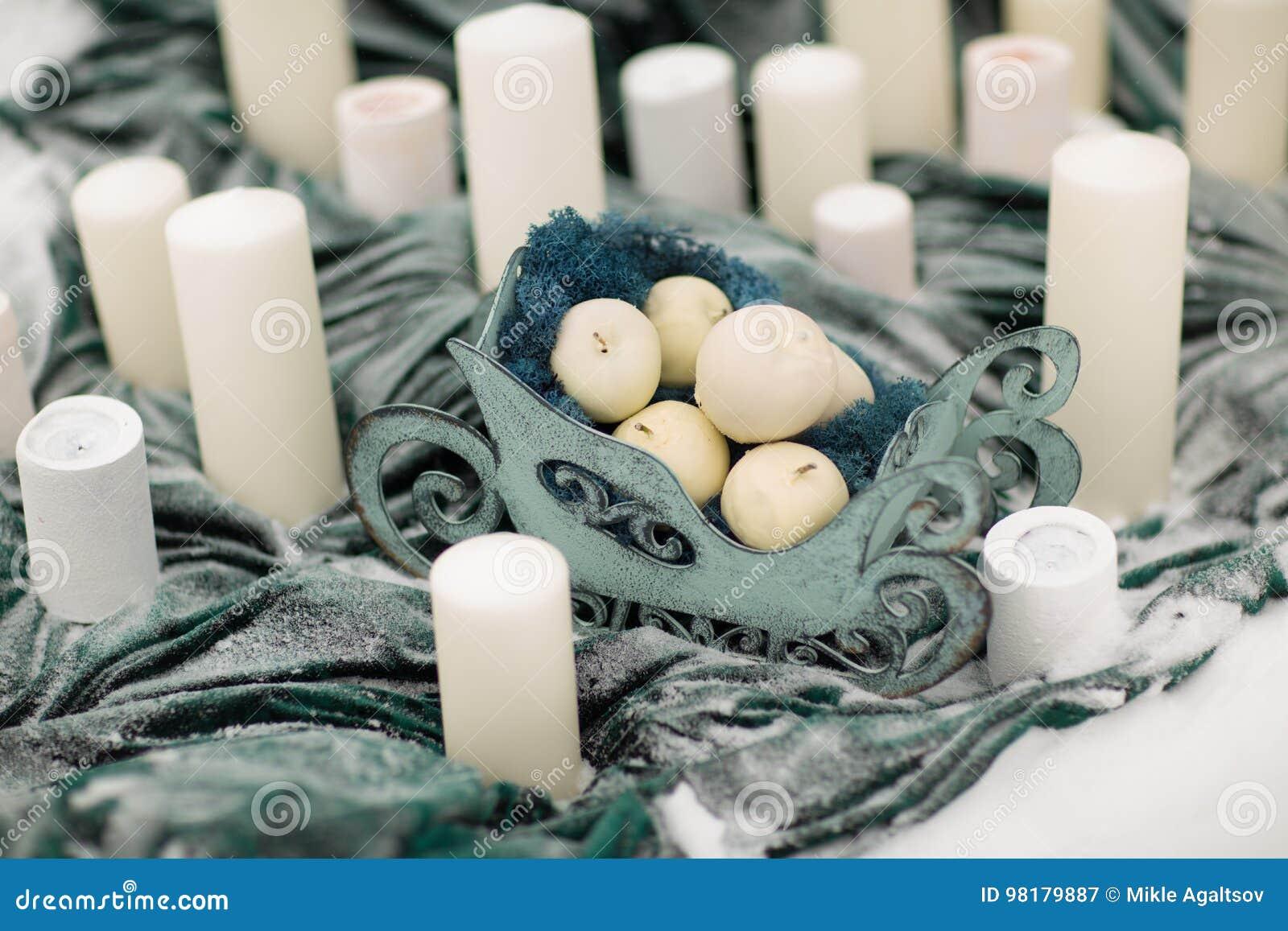 Adorne las velas con las flores y la nieve del invierno