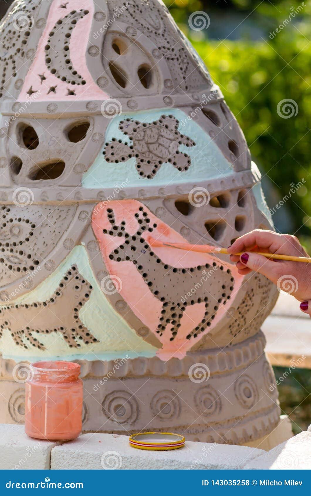 Adorne y esmalte un florero de la arcilla antes de que se cueza en el fuego La mano de una mujer con un cepillo lleva un esmalte
