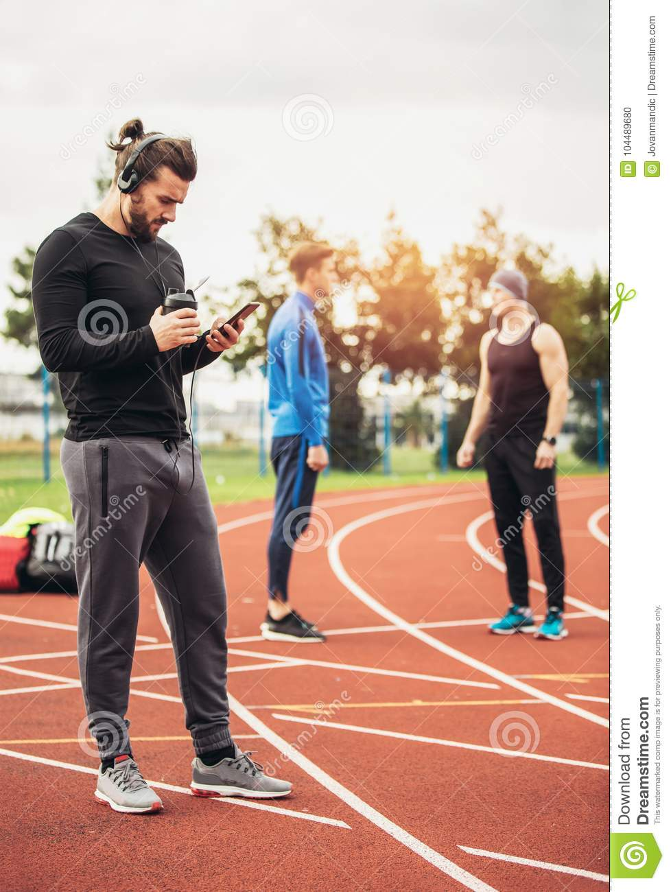 Athlete Man Using Mobile Phone And Listen Music After