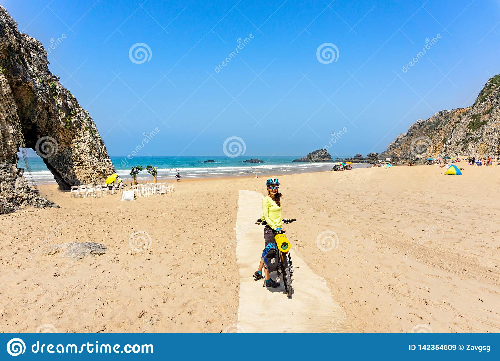 Adult attractive female cyclist with her bike is posing and smiling on a ocean beach. Portugal, Europe