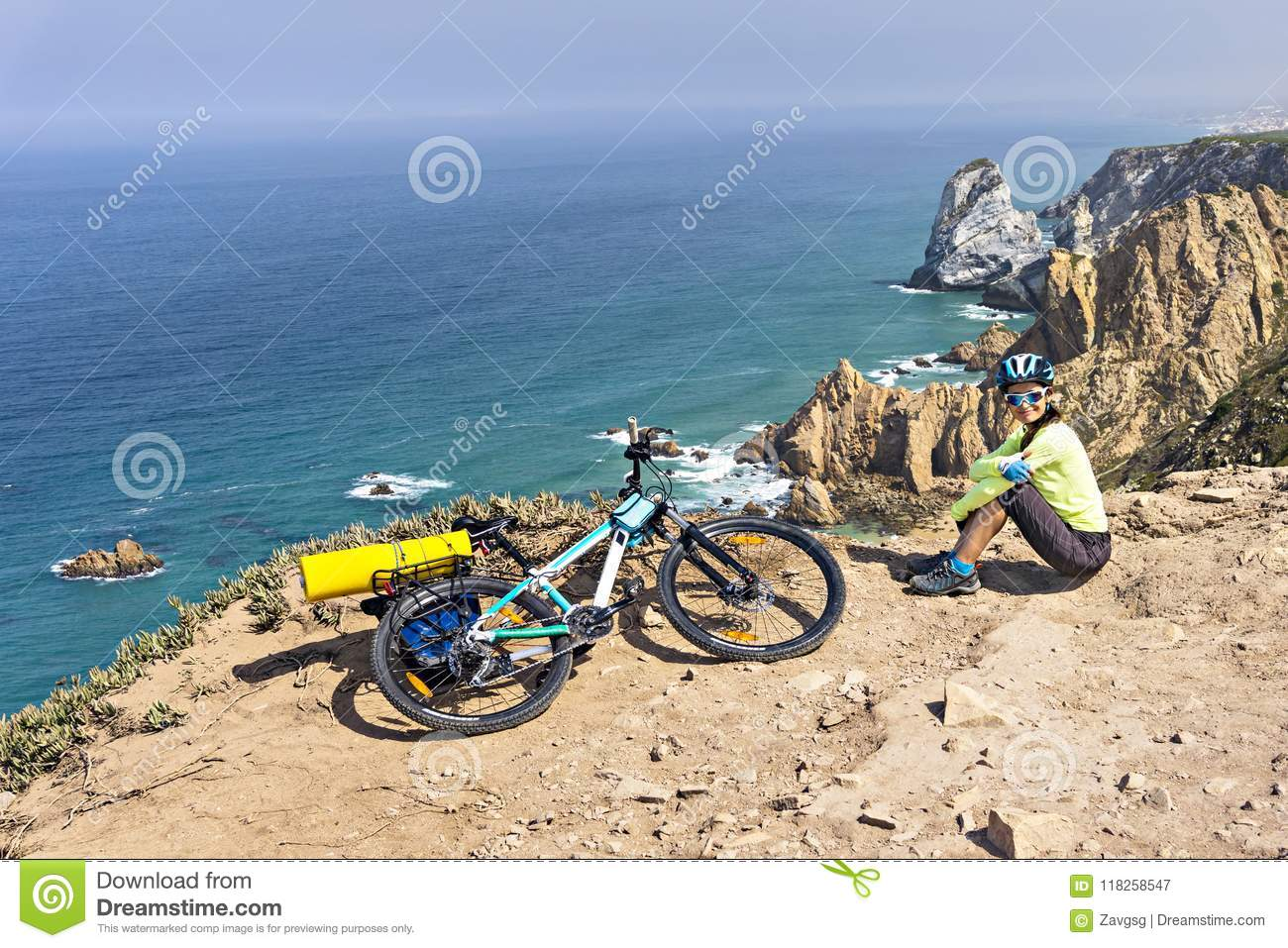 Adult attractive female cyclist poses on a ocean rocky coast.