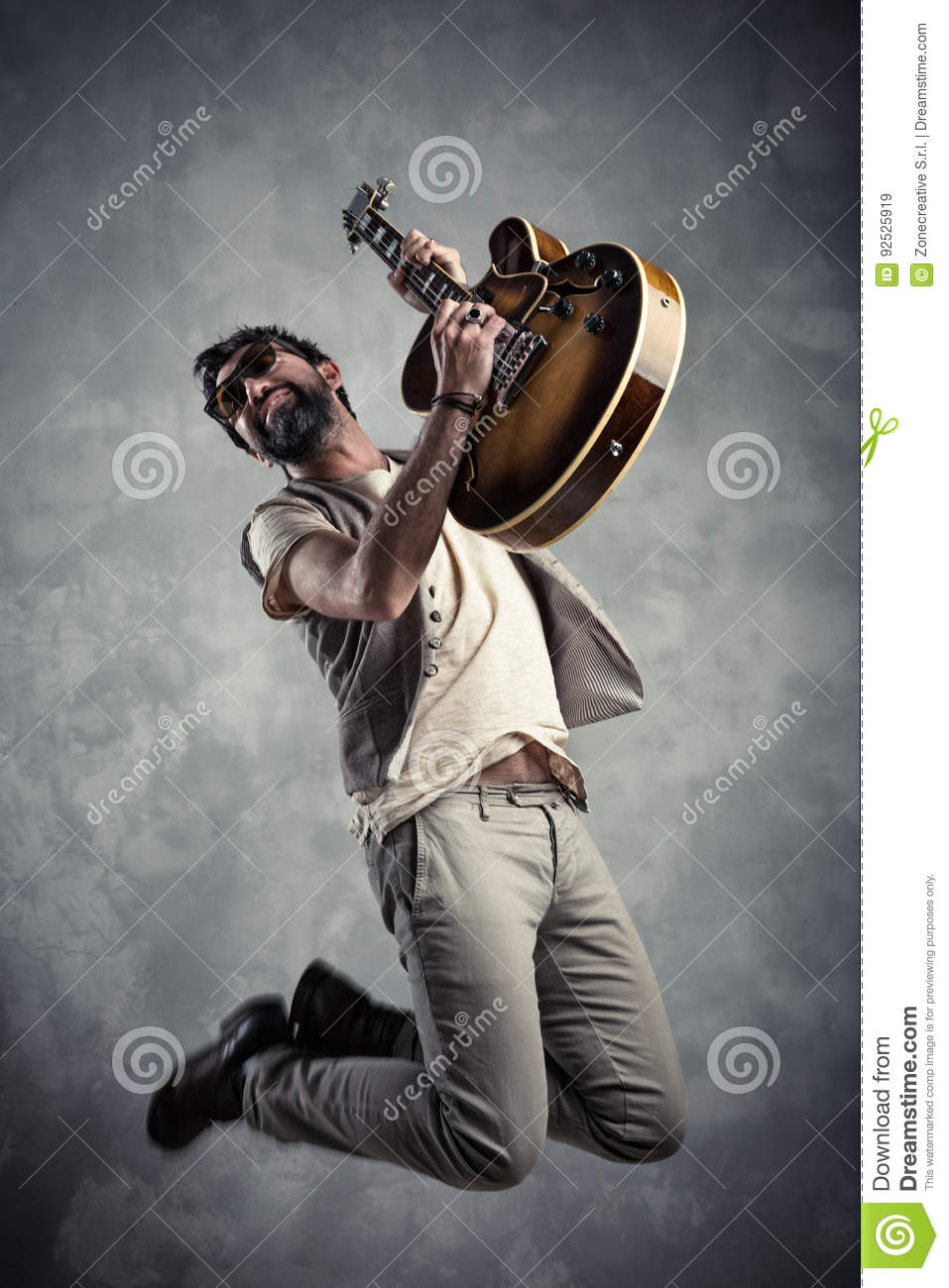 Adult caucasian guitarist portrait playing electric guitar and jumping on grunge background. Music singer modern concept