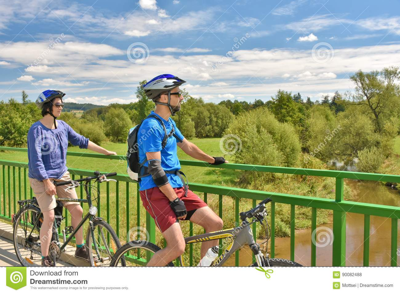 Adult couple on bikes stopping on a bridge