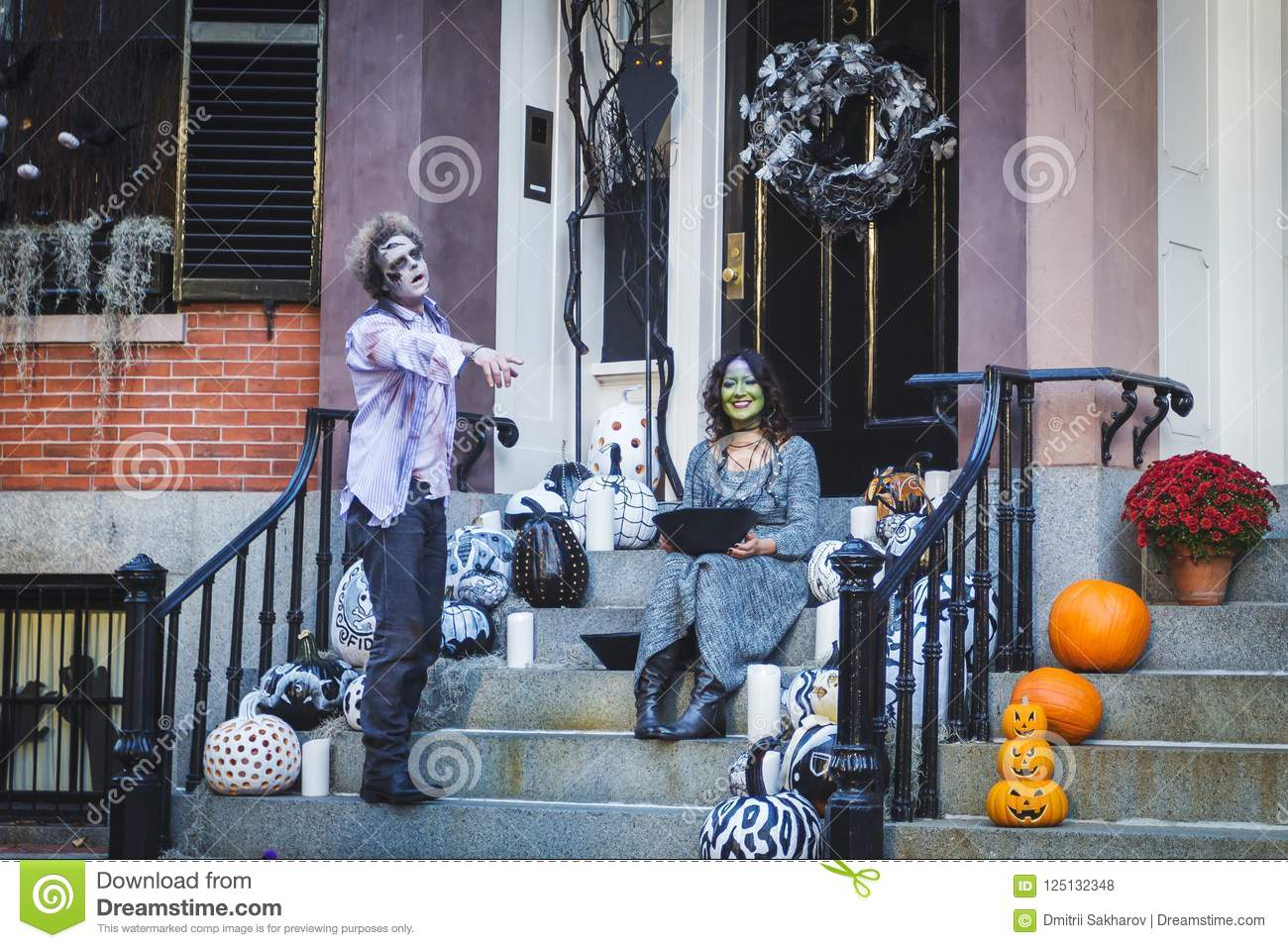 Adult couple dressed like zombie and a witch posing near their house on Halloween
