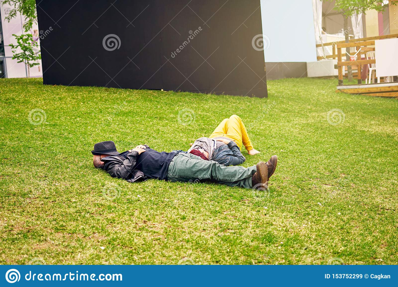 Adult couple lying on the grass field and taking a nap. Man`s face is covered with his hat. Editorial