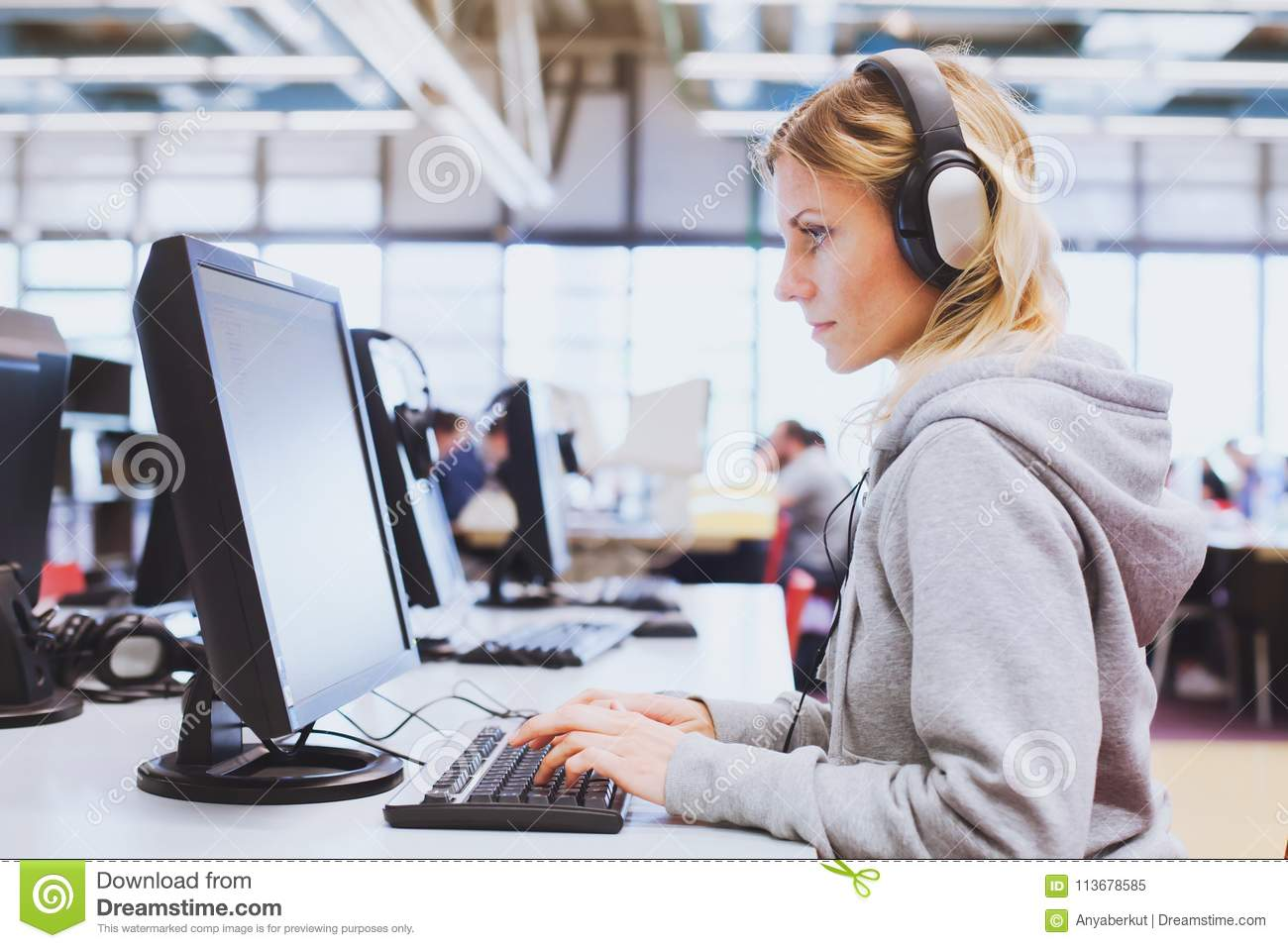 Adult education, student in headphones working on computer in the library