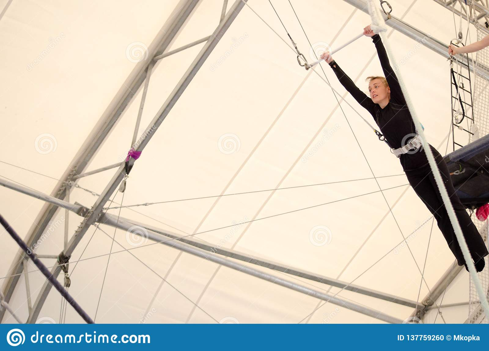 An adult female hangs on a flying trapeze at an indoor gym. The woman is an amateur trapeze artist