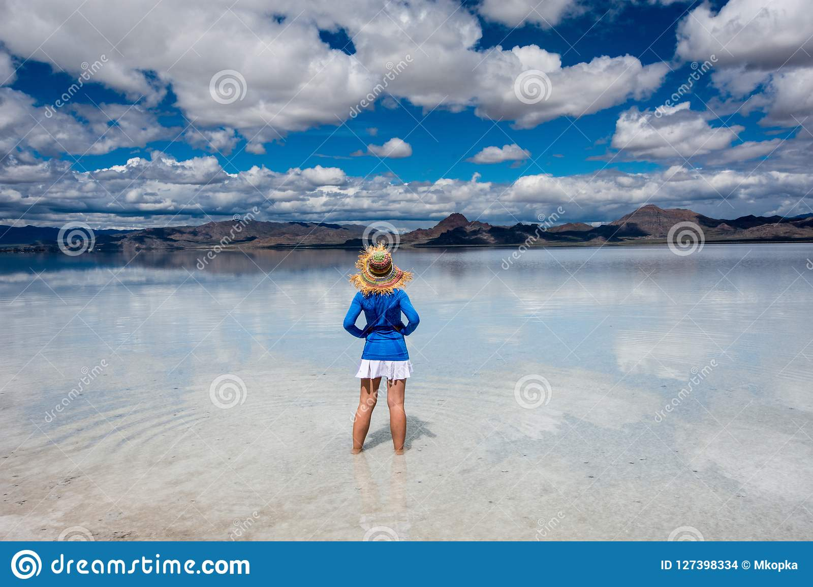 Adult female wears a straw hat posing at the Bonneville Salt Flats in Western Utah