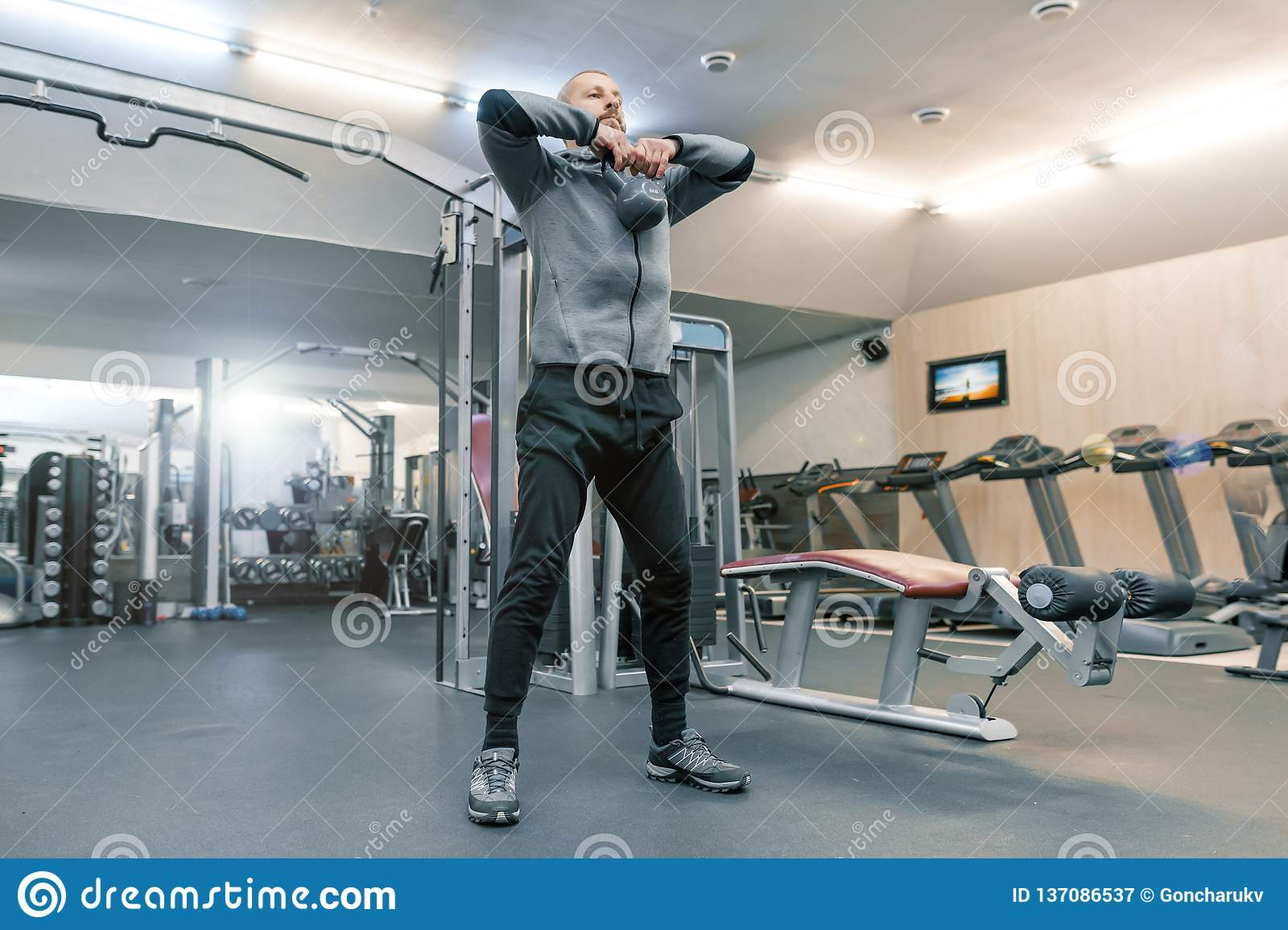 Adult handsome bearded man doing physical exercises in the gym. Sport rehabilitation, age, healthy lifestyle concept