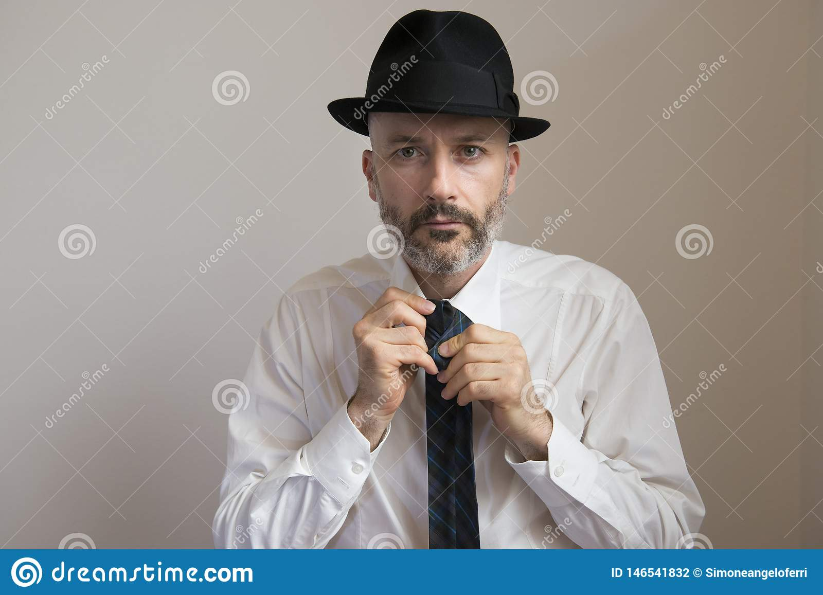 Adult man with hat and beard is knotting his necktie