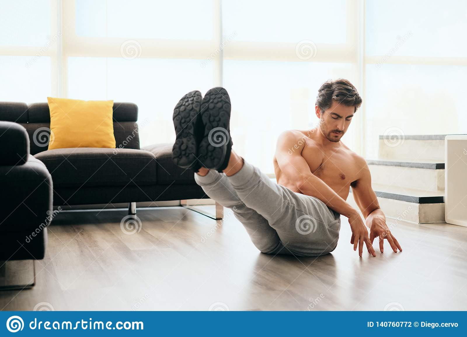 Adult Man Training ABS Muscles At Home Doing Russina Twist Exercise