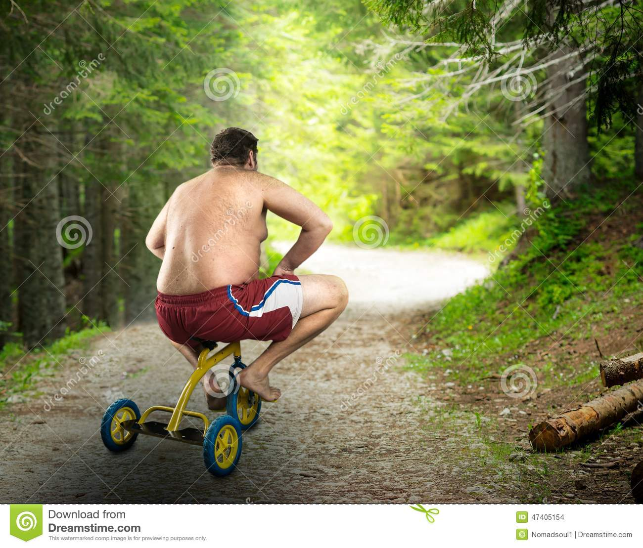 Adult naked man cycling on child s bicycle