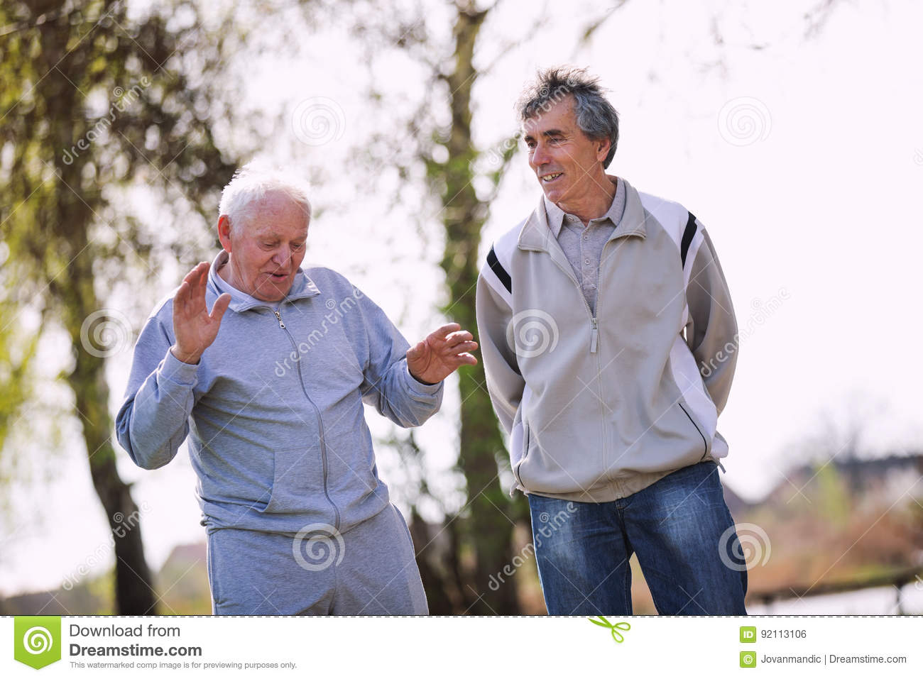 Adult son walking with his senior father