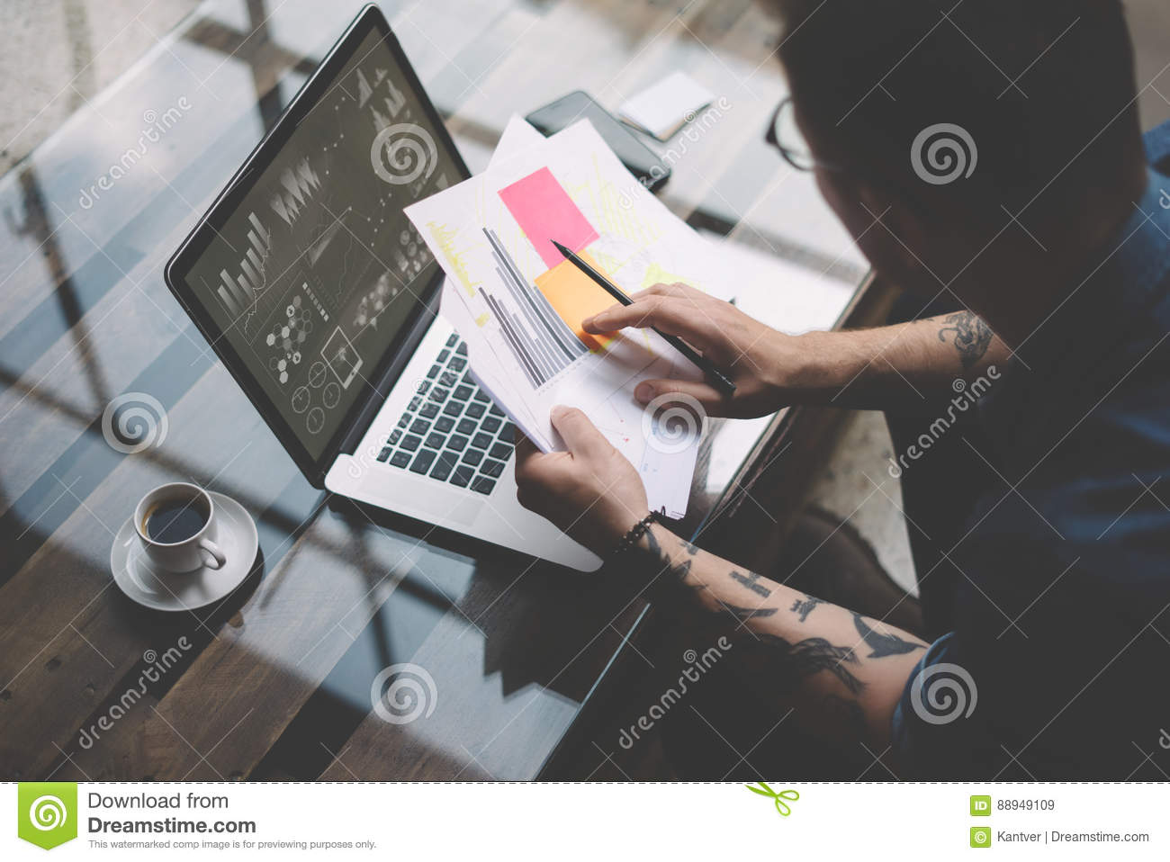 Adult Tattooed Coworker Working With Laptop At Workplace