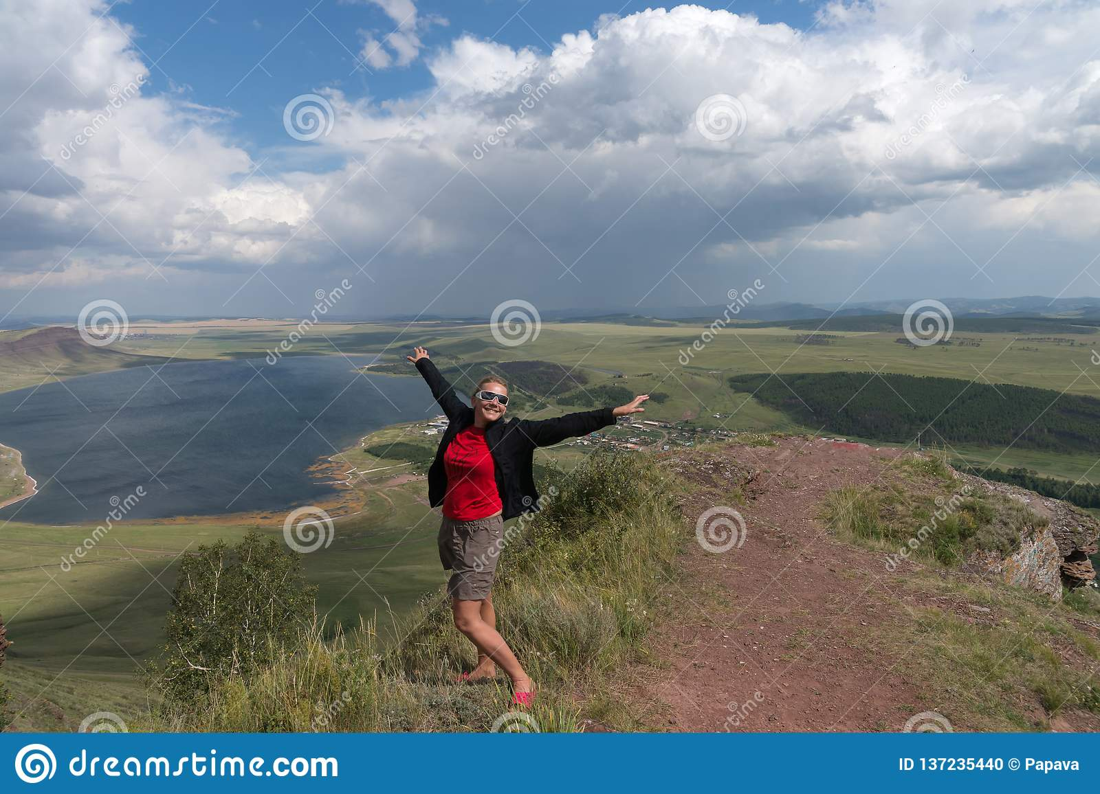 An adult woman stands, arms outstretched, on a high mountain, against the backdrop of a lake and a cloudy sky