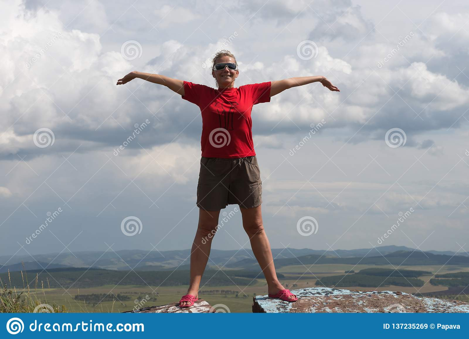 An adult woman stands, arms outstretched, on a high mountain, against the backdrop of a plain and a cloudy sky.