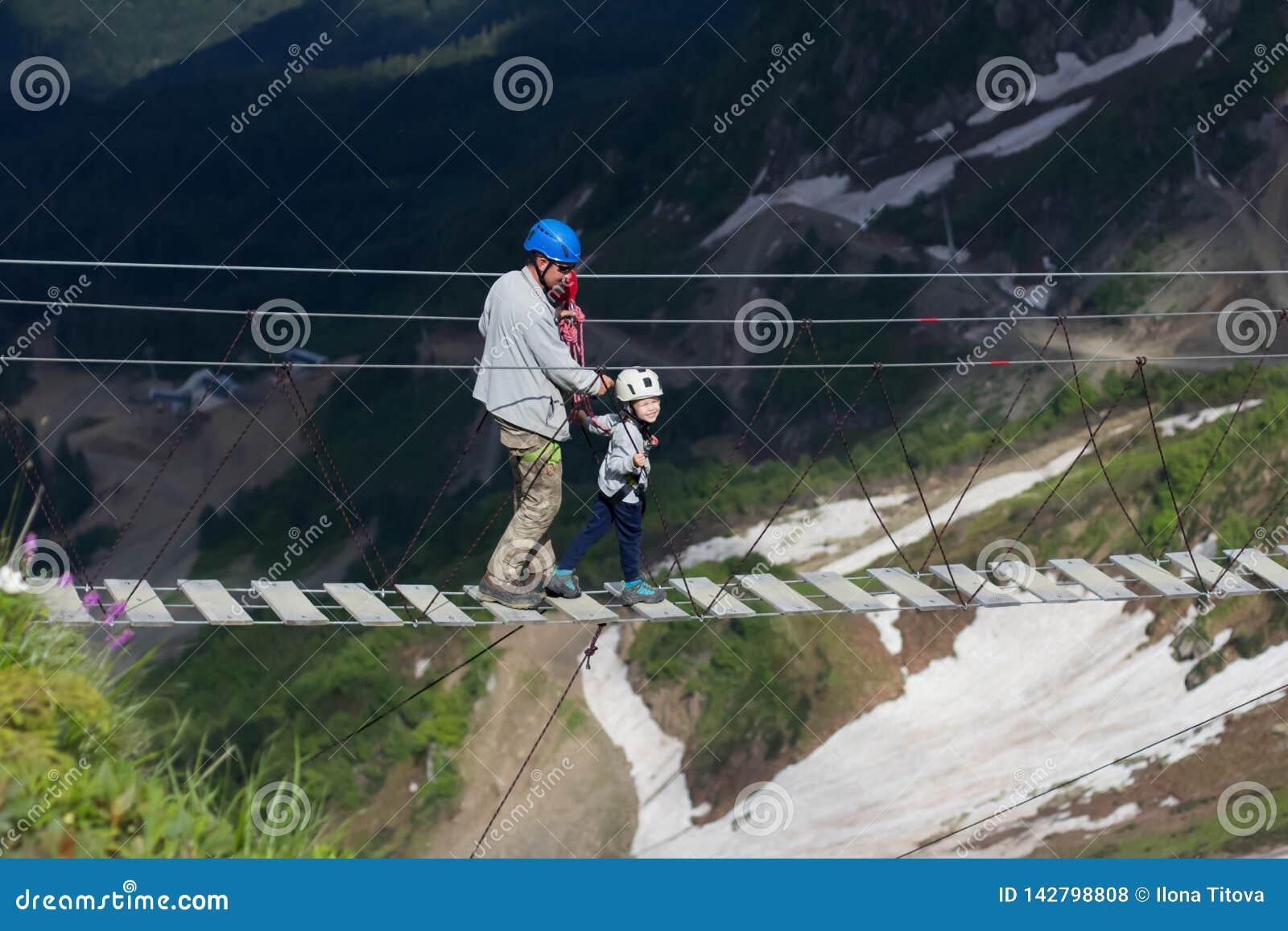 Adulto e criança em uma ponte de corda nas montanhas