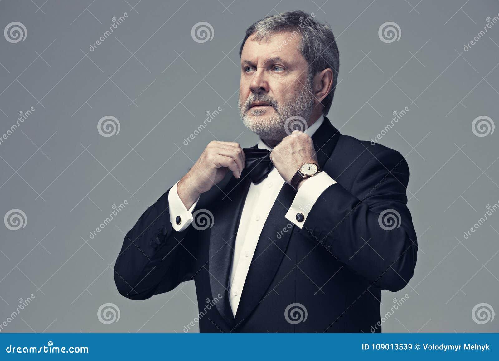 Adulto maschio invecchiato mezzo che indossa un vestito isolato su gray